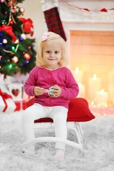 リビングルームの面白い女の子と表面のクリスマスツリー