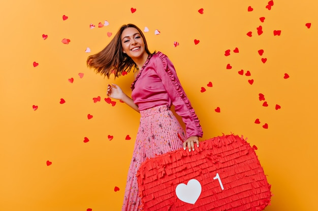 핑크 블라우스 춤에 재미 있은 소녀. 색종이와 초상화 촬영을 즐기는 놀라운 백인 모델.