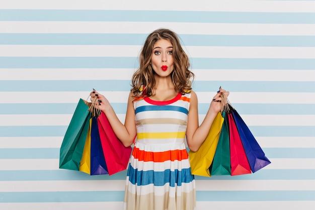Смешная девочка в полосатом платье позирует с выражением лица поцелуи после покупок. гламурная молодая женщина с вьющимися волосами, держащая сумки из бутика.