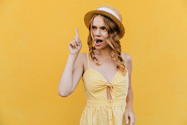 スタイリッシュな黄色のドレスのポーズで面白い女の子。周りを見回す麦わら帽子に興味のある女性モデル。
