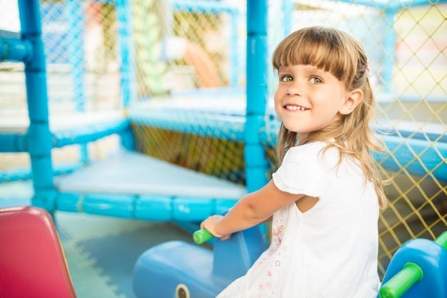 子供の娯楽センターの白いドレスを着た面白い女の子が笑顔でカメラを見る