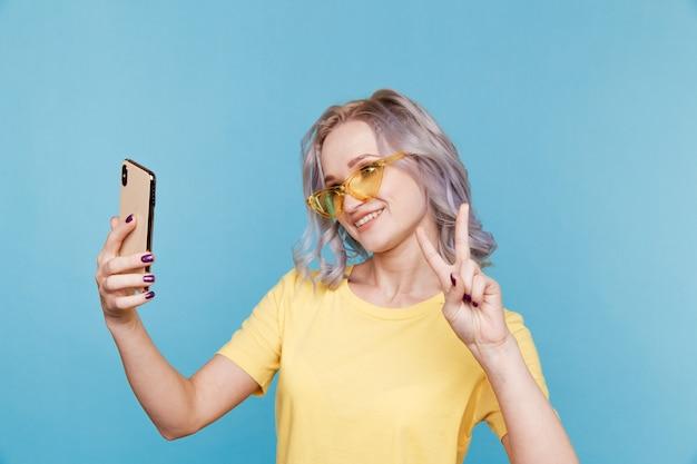 Смешная девочка в желтой одежде и очках, делая фото на свой телефон в голубой комнате.