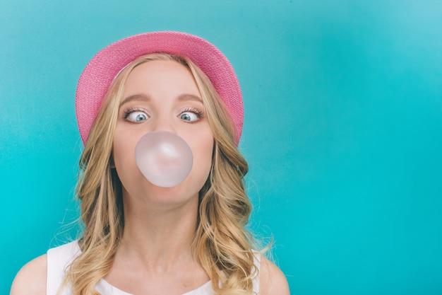 Смешная девчонка надувает шарик от жвачки
