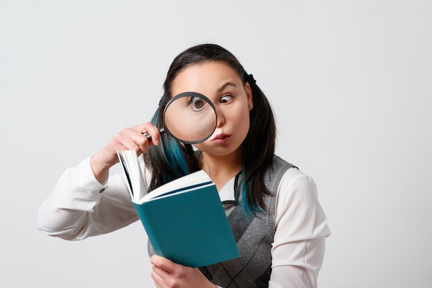 Funny girl looking at a book through a magnifying glass. on a grey light background