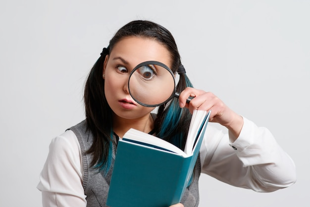 Funny girl looking at a book through a magnifying glass