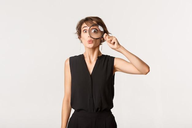 驚いた顔で虫眼鏡を通して見ている面白い女の子
