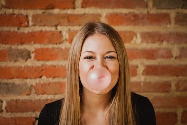 Funny girl making a pomp with a bubble gum