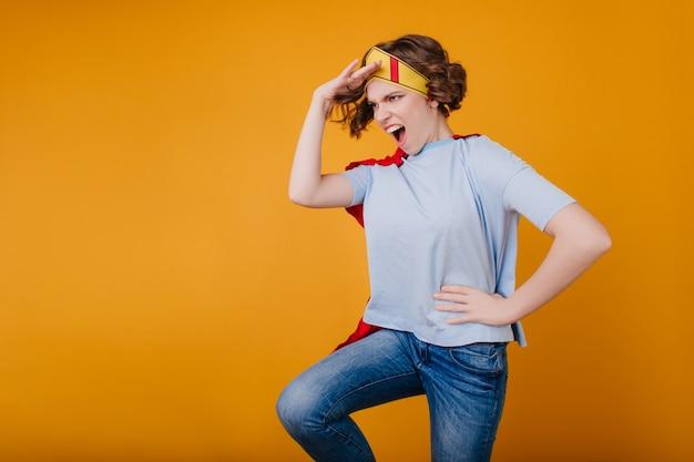 Ragazza divertente in corona di carta gialla scherzare sul servizio fotografico