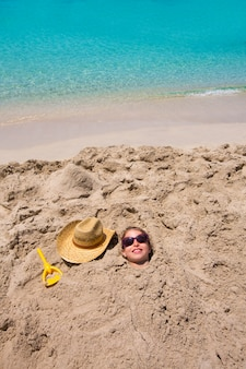 Funny girl playing buried in beach sand smiling sunglasses