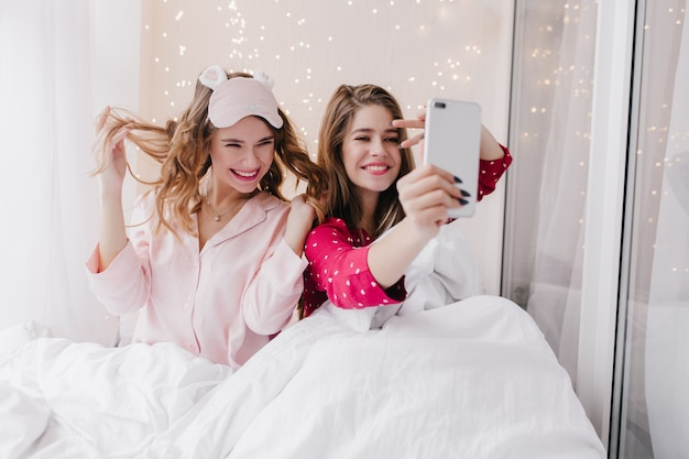 Funny girl playing with her curly hair in bed. lovable caucasian female model making selfie in morning.