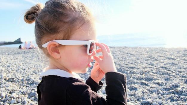 Смешная девочка играет с очками на галечном пляже на закате