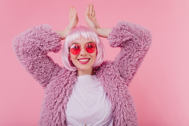Funny girl posing on pink wall. indoor photo of smiling winsome lady in fur jacket standing with hands up