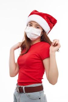 Забавная девочка красная футболка медицинская маска санта шляпа. фото высокого качества