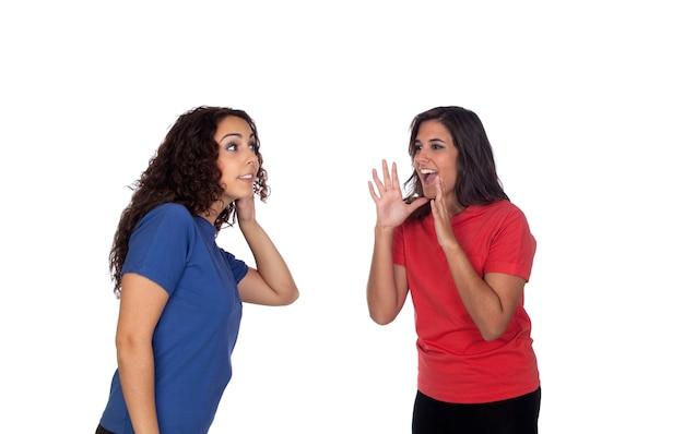흰색 배경에 고립 된 그녀의 친구에게 뭔가 외치는 재미 있은 소녀
