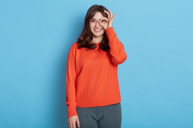 眼鏡のように彼女の手でokサインを身振りで示し、幸せな笑顔でカメラを見て面白い女の子
