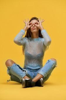 Смешная девочка сидит с прижатыми губами, показывая очки пальцами