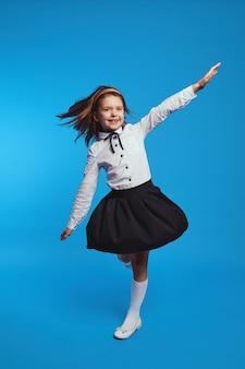 Смешная девочка быстро вращается в платье школьной формы, из-за чего оно вспыхивает