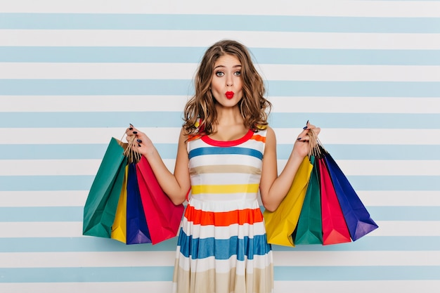 Ragazza divertente in vestito a strisce in posa con l'espressione del viso baciante dopo lo shopping. affascinante giovane donna con i capelli ricci che tengono i sacchetti dalla boutique.