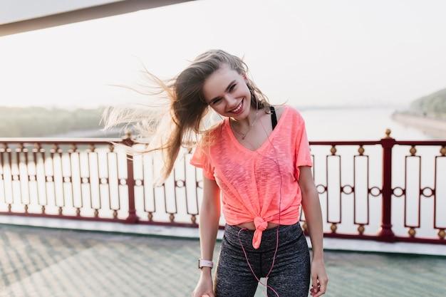 Ragazza divertente in abiti sportivi alla moda in posa sulla strada. colpo all'aperto di graziosa donna bionda divertendosi mattina.