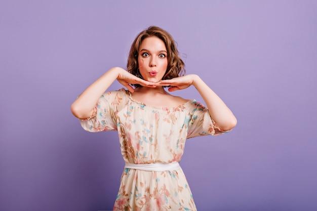 La ragazza divertente indossa un vestito con motivo floreale a scherzare sul servizio fotografico al coperto