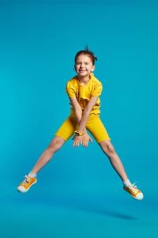 Смешная девочка в желтой спортивной одежде прыгает на цветном синем фоне