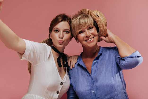 Funny girl in white dress making selfie with happy woman with blonde short hair in blue outfit and straw hat on pink backdrop.