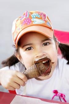 チョコレートアイスクリームを食べながらカメラを見ているキャップを持つ面白い女の子