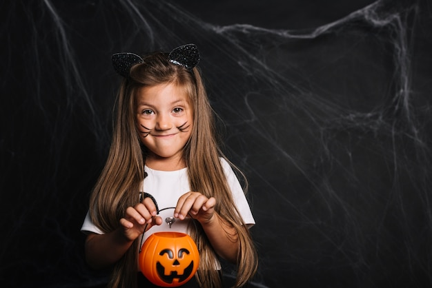 Funny girl with cat ears and trick or treat bucket