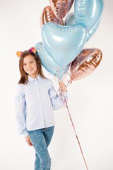 Смешная девчонка с кошачьими ушами, держа воздушные шары. концепт дня рождения