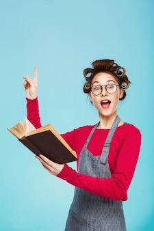 Смешная девчонка с бигуди и очки читает и указывает