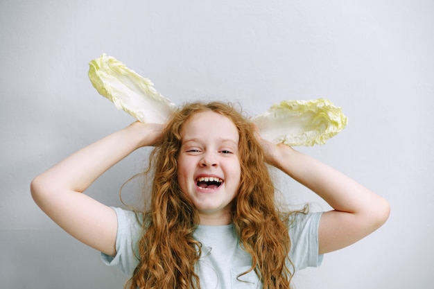 Funny girl with ears of peking cabbage.