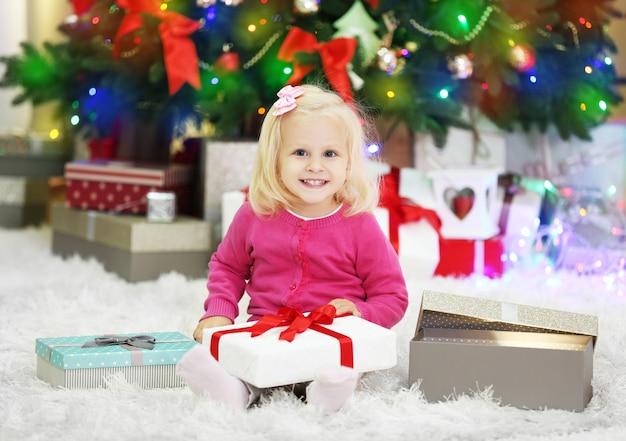 배경에 선물 상자와 크리스마스 트리가 있는 재미있는 소녀