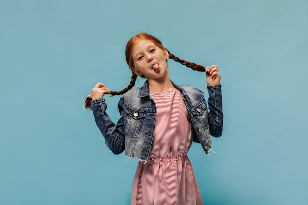 Funny girl with ginger hair and freckles in striped red dress and fashionable cool jacket showing tongues on blue wall