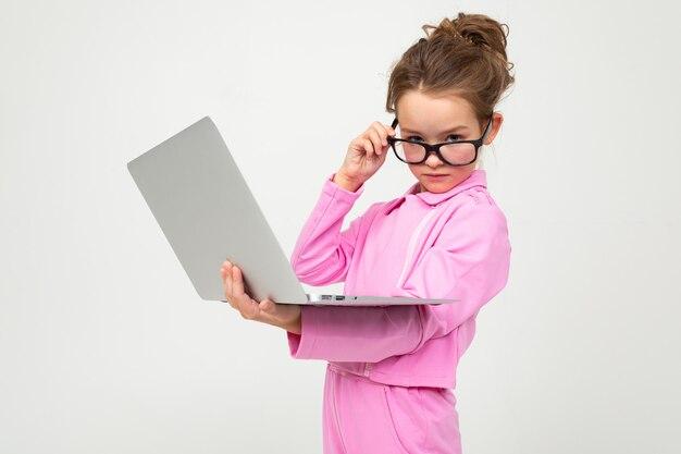 白いスタジオの壁にラップトップとピンクのスーツで眼鏡の面白い女の子