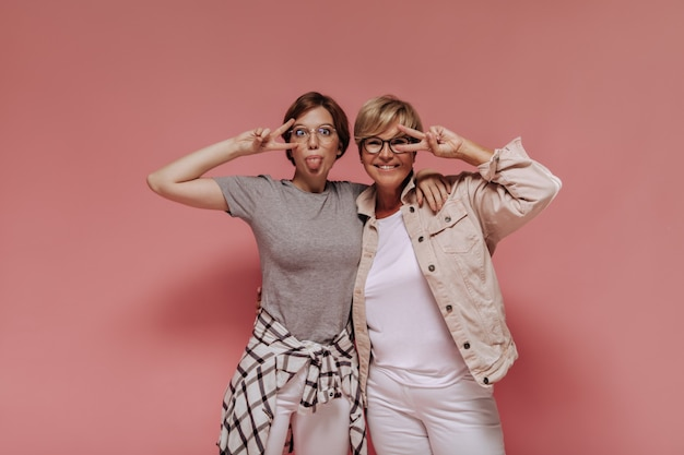 Funny girl with glasses in plaid shirt showing tongue and peace sign together with blonde lady in light clothes on pink background.