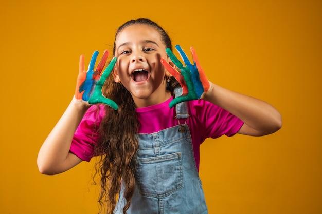 Смешная девочка с руками, окрашенными цветной краской.