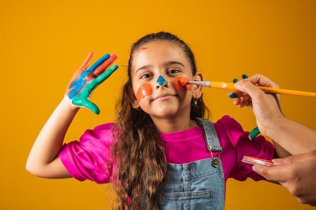 Смешная девочка с руками, окрашенными цветной краской. девушка рисует краской и кистью