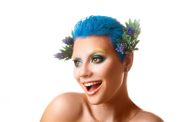 Funny girl with multicolor makeup smiling on white background isolated studio shot