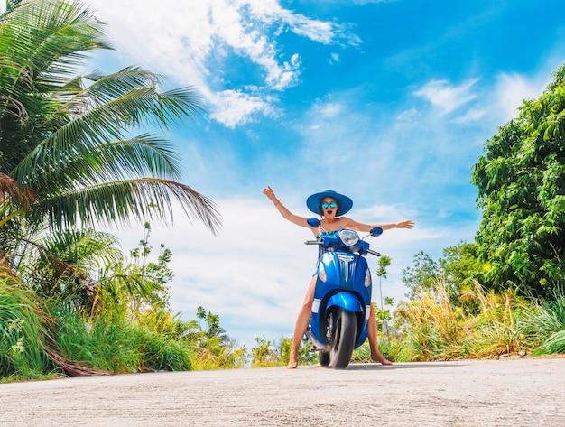 푸른 하늘과 녹색 열대 배경에 오토바이를 타고 열린 손으로 재미있는 여자