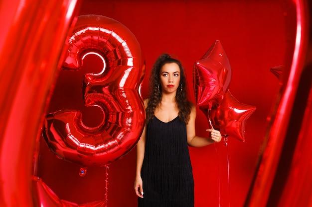 赤い背景に赤い風船を持つ面白い女の子の形の風船で若い女性のお祭り気分...