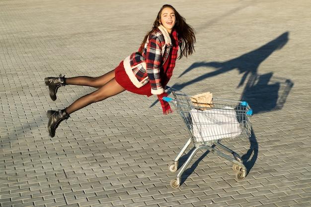 ショッピングカートを持つ面白い女の子。ショッピングのコンセプト。屋外のショップカートと幸せな女性。