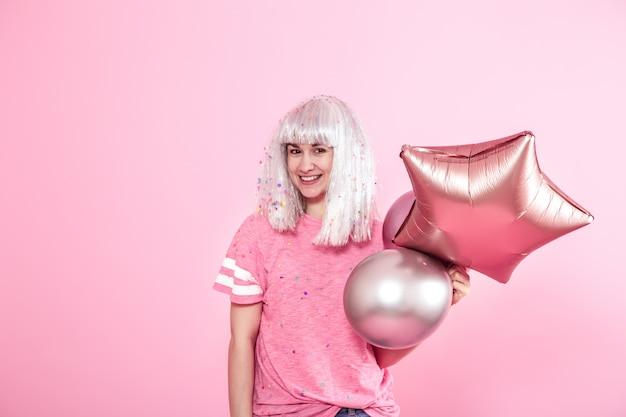 ピンクの壁に銀髪の面白い女の子が笑顔と感情を与えます。風船と紙吹雪の若い女性または十代の少女