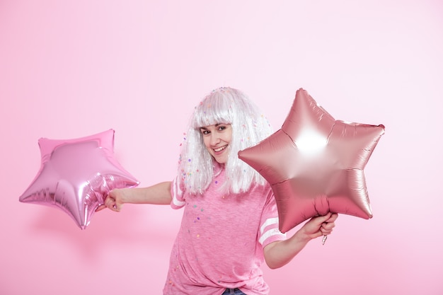 Funny girl with silver hair gives a smile and emotion on pink background. young woman or teen girl with balloons and confetti
