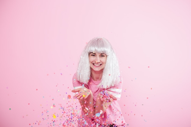 Funny girl with silver hair gives a smile and emotion on pink background. young woman or teen girl with confetti