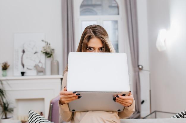 Ragazza divertente con manicure nera alla moda che nasconde la faccia dietro il computer portatile