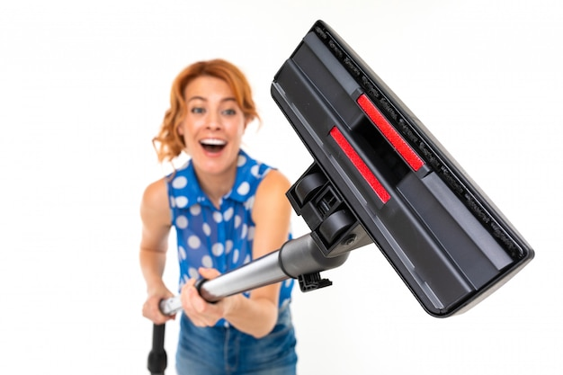 Funny girl with a vacuum cleaner on a white wall