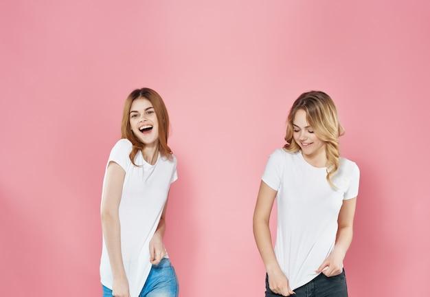 흰색 티셔츠를 입은 재미있는 여자 친구는 감정을 껴안고 재미있는 우정을 나눈다. 고품질 사진