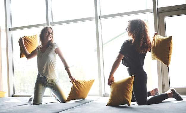 Веселые подружки играют в подушки, возле больших окон.