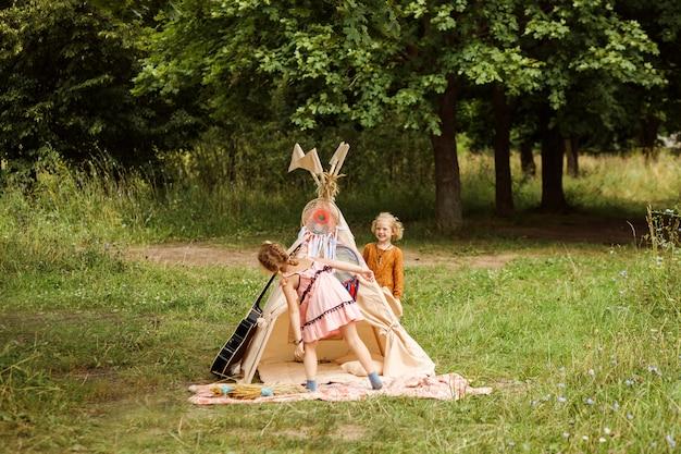 웃긴 소녀들이 위그 암 옆에서 놀고 있습니다. 아이들은 보헤미안 또는 히피 스타일의 옷을 입고 숨바꼭질을합니다. 여름철, 숲이나 공원에서 야외. 가족 주말.