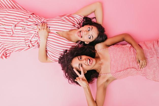 Веселые девчонки дурачатся и показывают языки во время позирования. дамы в полосатых платьях лежат на полу.